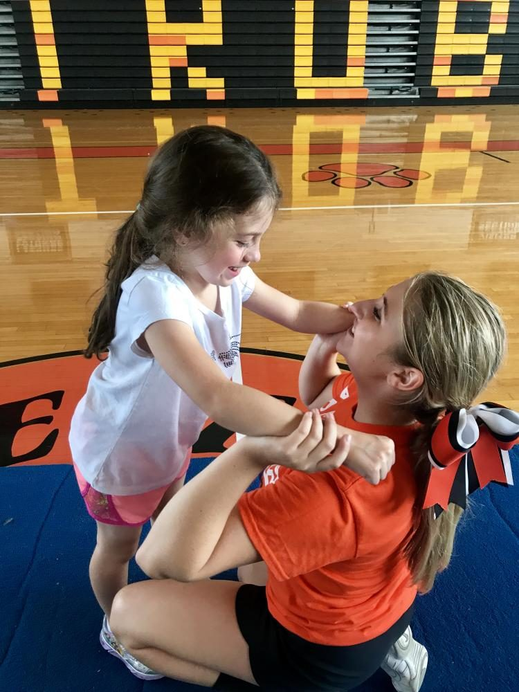 Ada DiFrancesco is in the hands of Senior Raven Dupilka. With the help of Raven, Ada was able to overcome the challenge of having a hearing disability to have a great time at this year's Mini Cheer Camp.
