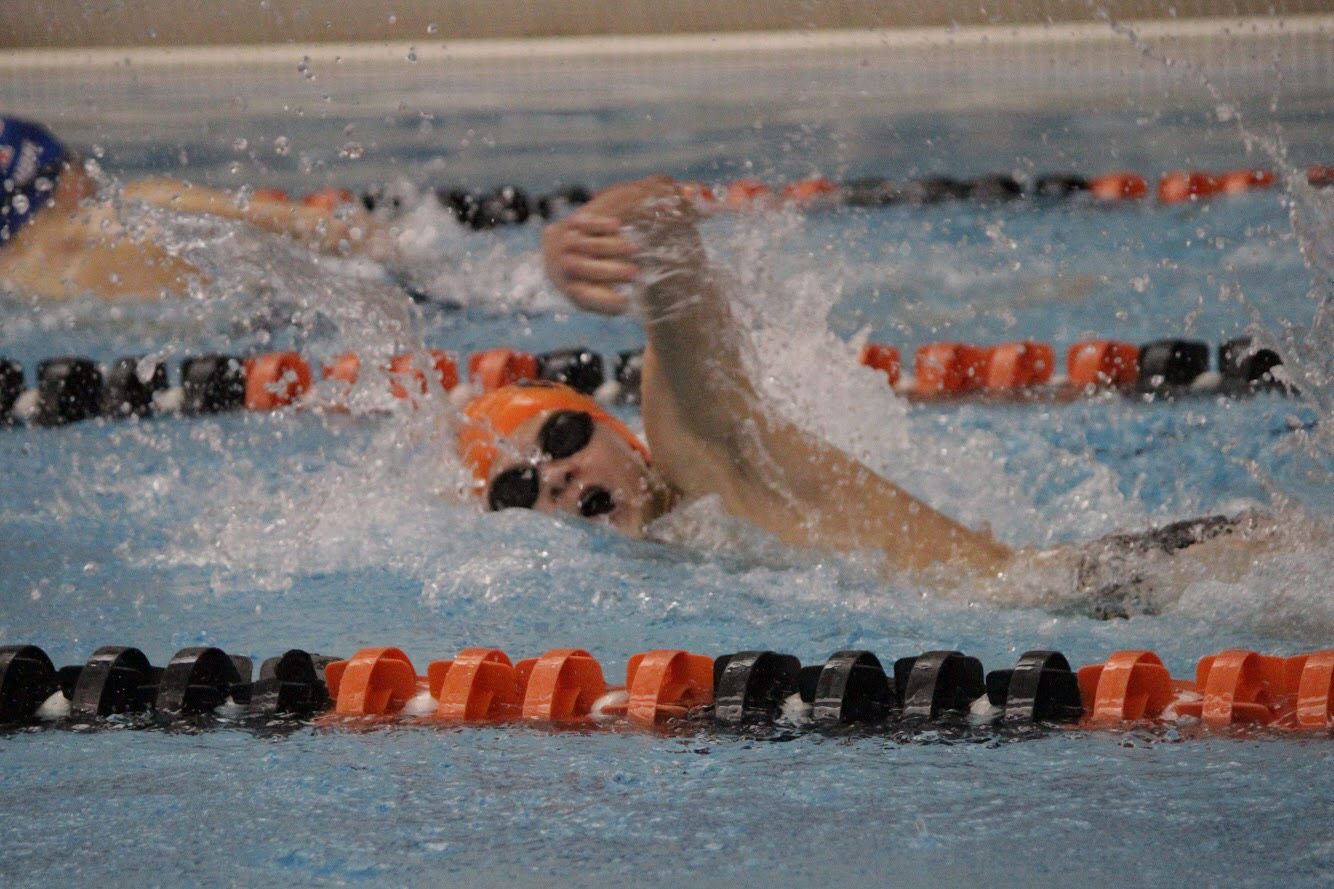 Freshman Colin Spehar takes a quick breath of air during his freestyle at the first swim meet of the season.