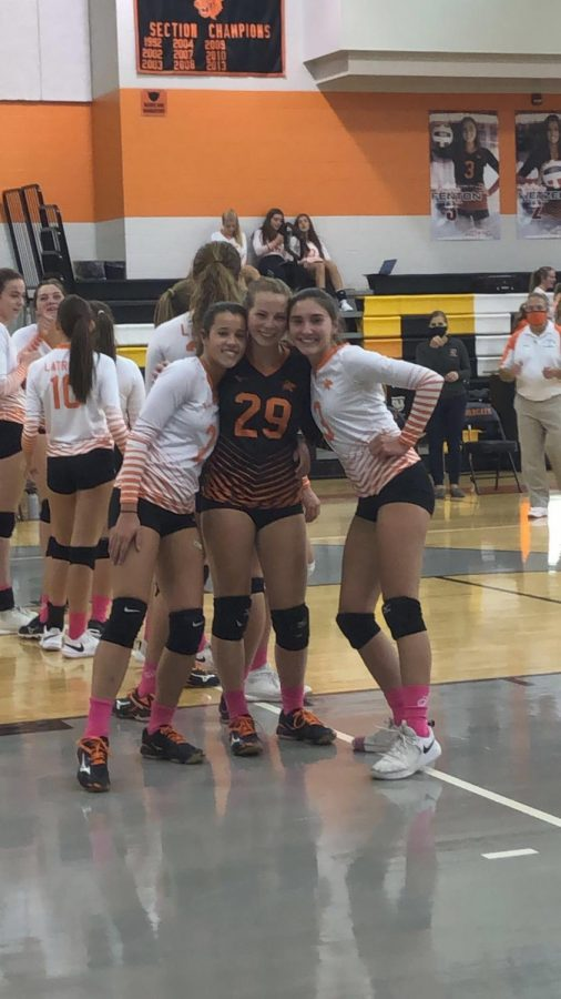 The girls varsity volleyball team at this point during the game are permitted to take their masks off to play, but the coaches are still practicing proper social distancing by staying six feet apart and wearing their masks.