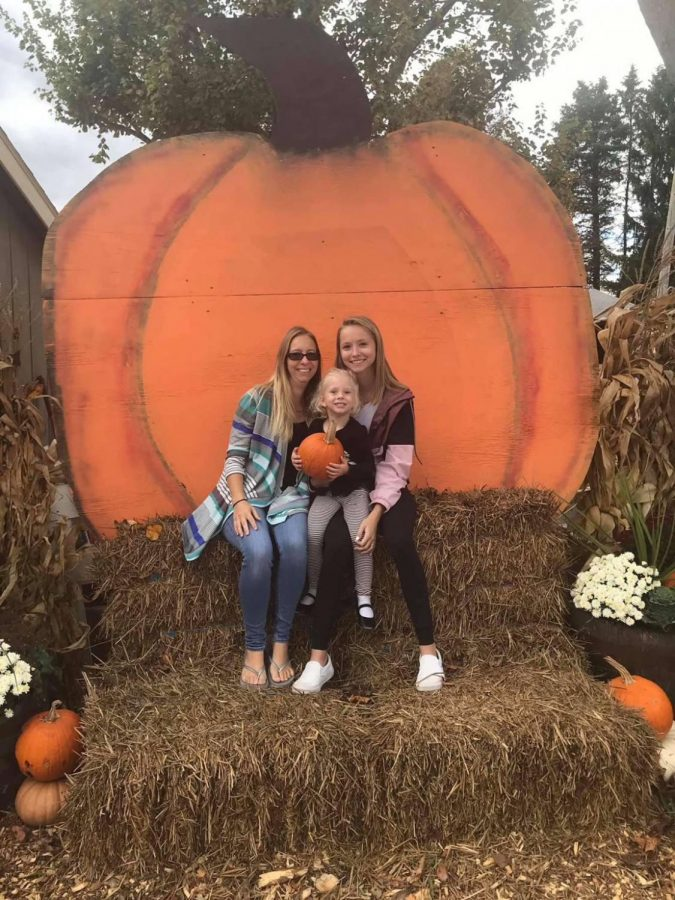 Hollie Culley, Daisy Wishard, and Chloe Culley smile cheerfully as they sit on a haybale in front of a large pumpkin cut out.