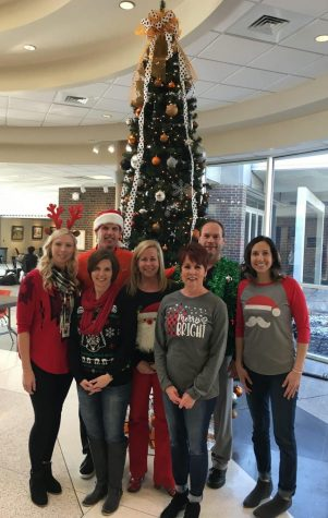 Latrobe Staff poses in front of the annual Christmas tree with Mrs. Sherwin.