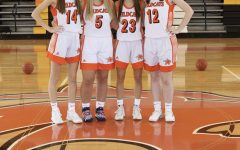 Seniors Lexi McNeil, Ava Vitula, Lexi Weatherton, and Rachel Ridilla standing on their home court and enjoying the team's picture day.
