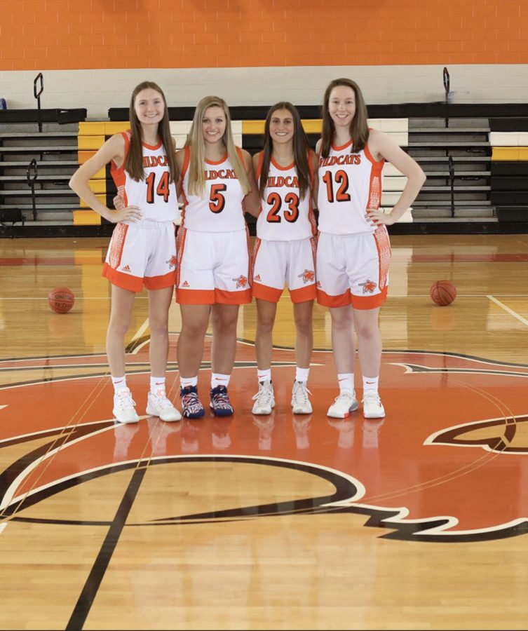 Seniors Lexi McNeil, Ava Vitula, Lexi Weatherton, and Rachel Ridilla standing on their home court and enjoying the teams picture day.