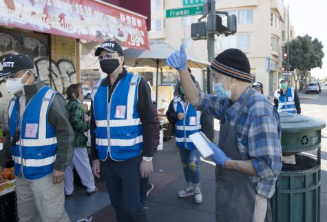 A small-business owner gives his thumb up to a volunteer patrol team in Oakland's Chinatown, California, on Saturday. LIU GUANGUAN/CHINA NEWS SERVICE